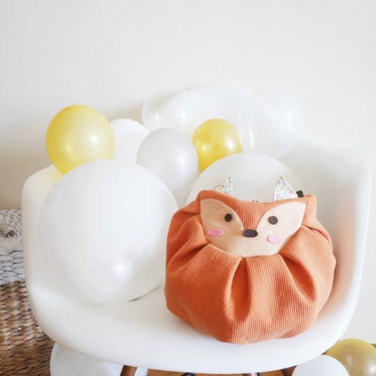orange fox mochi bag with balloons on chair